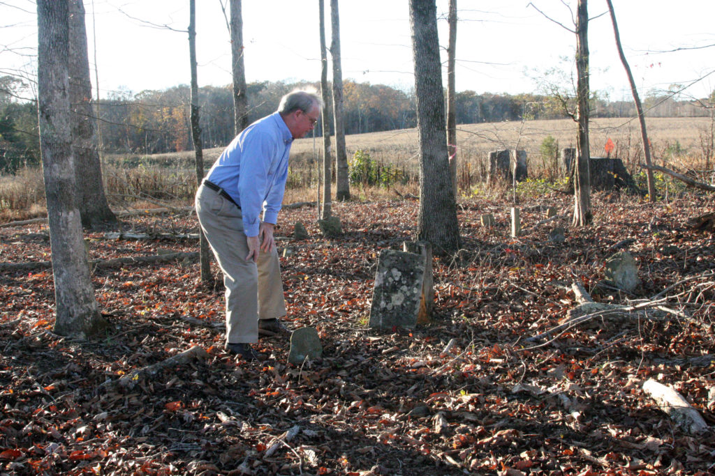 Solar project opponent Keith Gatlin checks out weather-worn headstones in an old slave cemetery that would abut a proposed industrial-scale generating station in Cool Springs. (CJ photo by Dan Way)