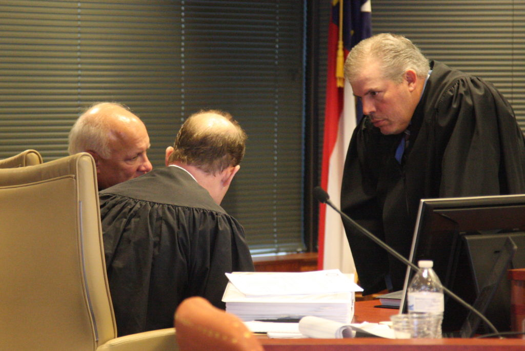 From left, Superior Court Judges Wayland Sermons of Beaufort County, Martin McGee of Cabarrus County, and W. Todd Pomeroy of Cleveland and Lincoln counties huddle Wednesday, Feb. 21, at the conclusion of a hearing of a suit seeking to throw out all laws passed in a 2016 special session. (CJ photo by Dan Way)