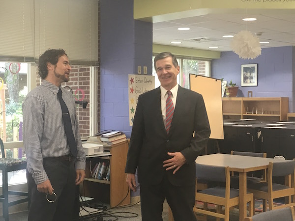 Stough Elementary Principal Chris Cox speaks with Gov. Roy Cooper at the school Tuesday, June 10. (Photo by Lindsay Marcello).