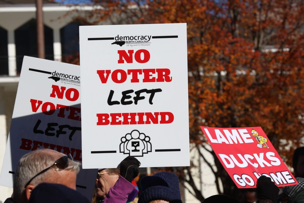 Opponents of North Carolina's new constitutionally mandated voter ID requirement protest outside the state Legislative Building on Nov. 27, 2018. (CJ photo by Don Carrington.)