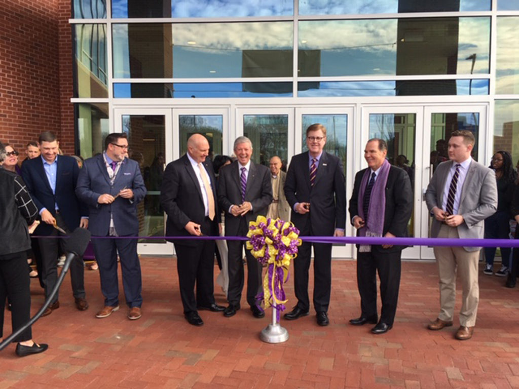 UNC Board of Governors Chairman Harry Smith (left of center, white shirt, scissors in hand) prepares to cut the ribbon commemorating the opening of the new student center at East Carolina University Jan. 7, 2019. Smith said in November 2018 he was ending all communications with ECU.