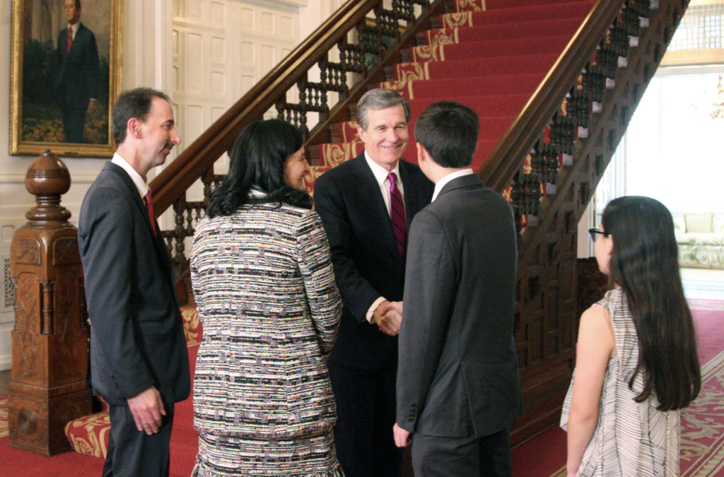 Gov. Roy Cooper congratulates family members of Appeals Court Judge Mark Davis (at left), whom Cooper appointed Monday to the N.C. Supreme Court. (CJ photo by Dan Way)
