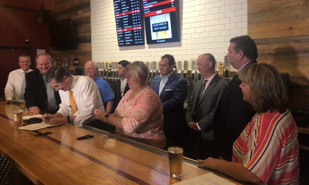 Gov. Roy Cooper signs House Bill 363, Craft Beer Modernization Act, joined by lawmakers, brewers, and lobbyists, May 30 at Raleigh Brewing Co. (CJ photo by John Trump)