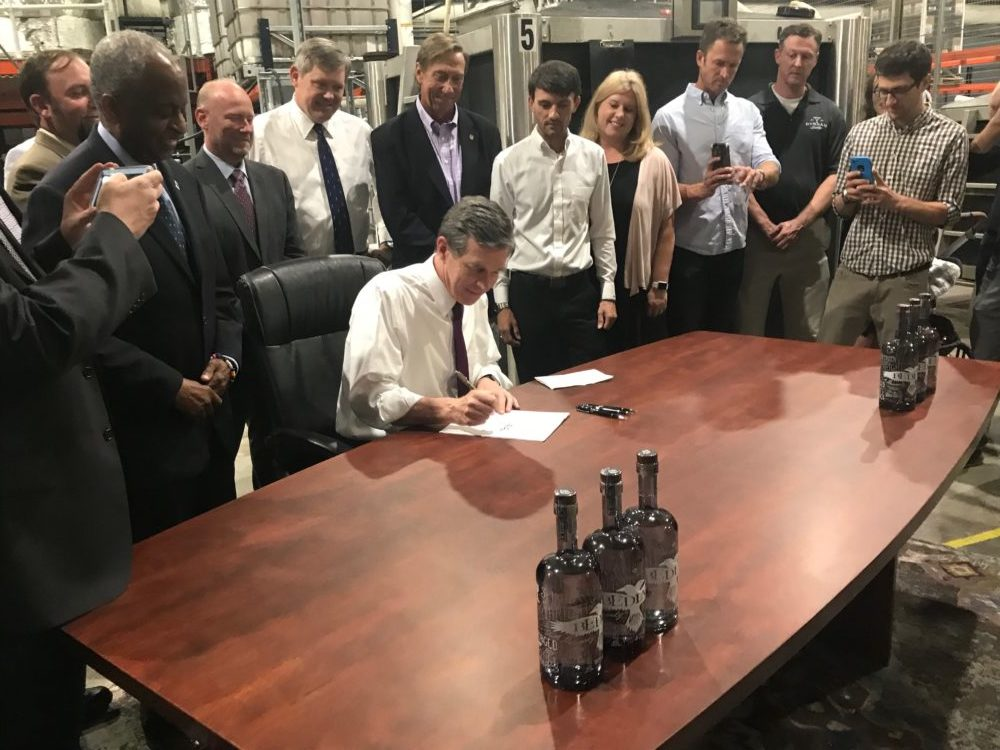 Gov. Roy Cooper signs Senate Bill 290 July 29, 2019 at Greybeard Distillery in Durham. (CJ photo by John Trump)