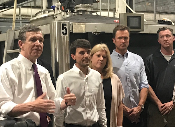 Gov. Roy Cooper, flanked by lawmakers and distillers, signed Senate Bill 290 on July 29 at Graybeard Distillery in Durham. (CJ photo by John Trump)
