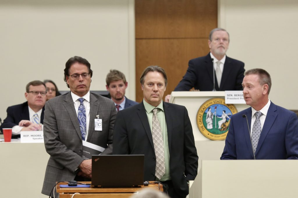 Eagle Intel Services investigators Frank Brostrom, Tom Beers, and Kevin Greene (front, from left) present their report to a legislative oversight committee Nov. 20, 2019. House Speaker Tim Moore, R-Cleveland is back row, left. Senate leader Phil Berger, R-Rockingham, is at the lectern. (CJ photo by Don Carrington)