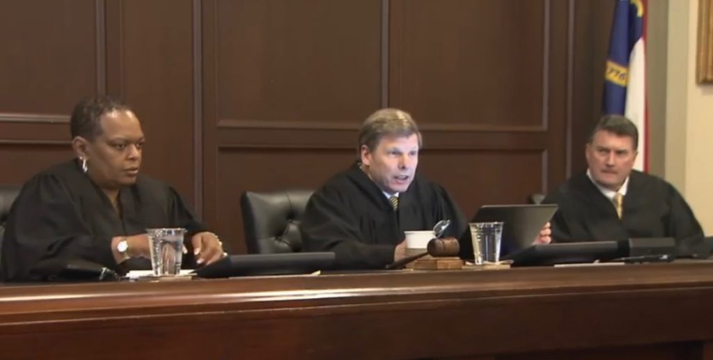 Superior Court Judges Alma Hinton, left, and Joseph Crosswhite, right, listen as Judge Paul Ridgeway reads the unanimous decision on Dec. 2, 2019, in the Harper v. Lewis congressional redistricting case. (WRAL.com screen shot)