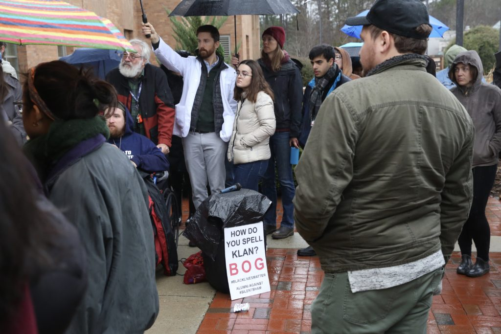 Protesters opposing the deal turning Silent Sam from UNC to the Sons of Confederate Veterans stand in the rain outside the system's office Friday, Dec. 13. (CJ photo by Don Carrington)