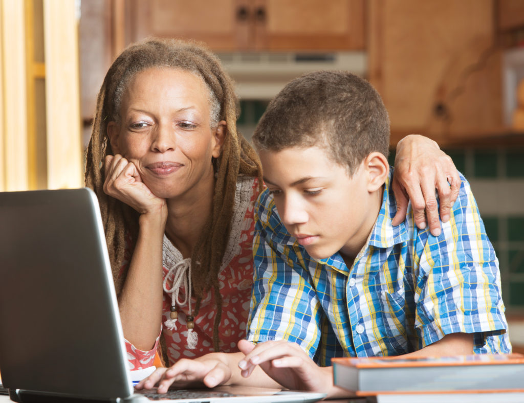 Mother overlooks as her teenaged son uses his laptop to study in their kitchen. (Stock photo)
