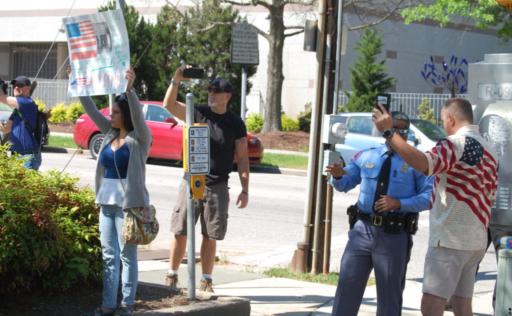 A Raleigh police captain speaks with ReopenNC protesters in Raleigh, April 14. (CJ photo by Rick Henderson)