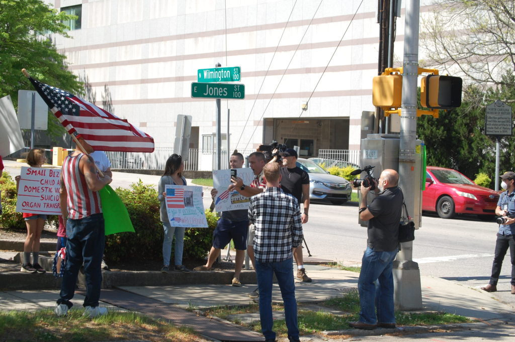 Leonard Harrison (near center, with cell phone) does a livestream of the April 14 protest by ReopenNC in Raleigh. (CJ photo by Rick Henderson)