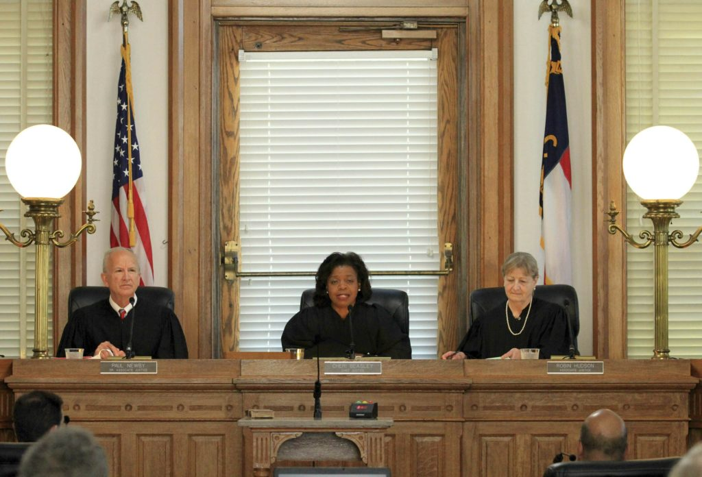 Senior Associate Justice Paul Newby, from left, Chief Justice Cheri Beasley and Associate Justice Robin Hudson preside at a special session of the Supreme Court of North Carolina at New Bern City Hall in New Bern, N.C., May 15, 2019. The May court session is part of the Supreme Court Bicentennial Anniversary celebration events in eastern North Carolina. (Gray Whitley/Sun Journal via AP)