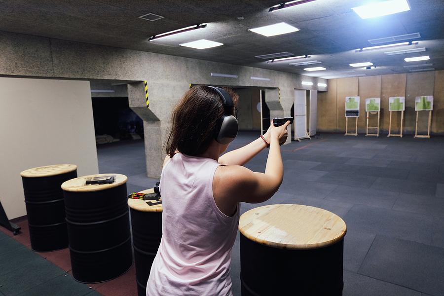 Girl in headphones shoots a gun in shooting range