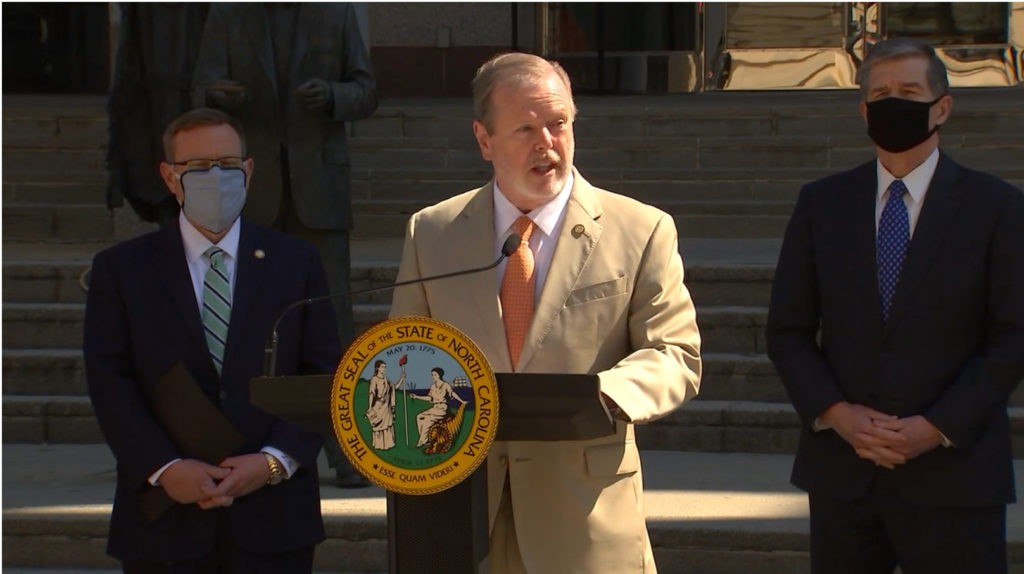 Senate leader Phil Berger, R-Rockingham, speaks as House Speaker Tim Moore, R-Cleveland, left, and Gov. Roy Cooper listen during a joint March 10, 2021, news conference. (Screen shot from abc11.com.)
