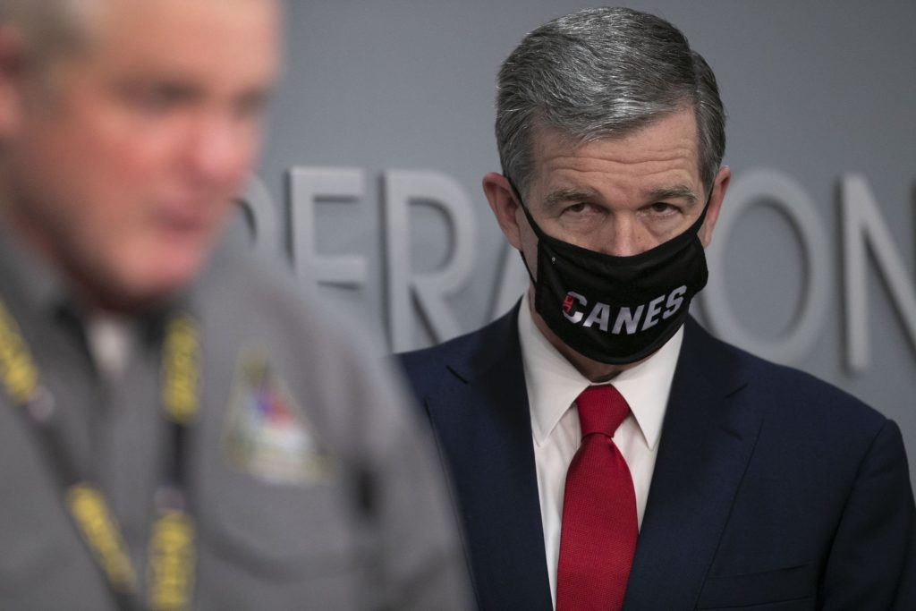 North Carolina Governor Roy Cooper listens to Mike Sprayberry, Director of Emergency Management, during a press briefing on the COVID-19 virus and vaccination efforts on Tuesday, March 2, 2021, at the Emergency Operations Center in Raleigh, N.C. (Robert Willett/The News & Observer via AP)