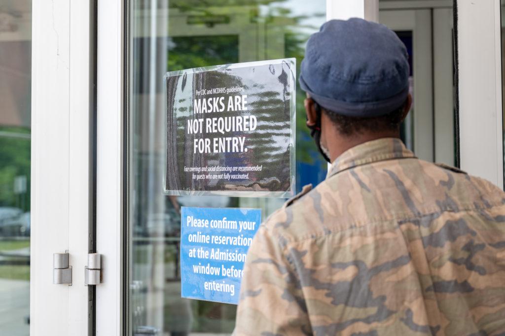 Man reads mask sign posted on Raleigh store. File photo by Maya Reagan, Carolina Journal