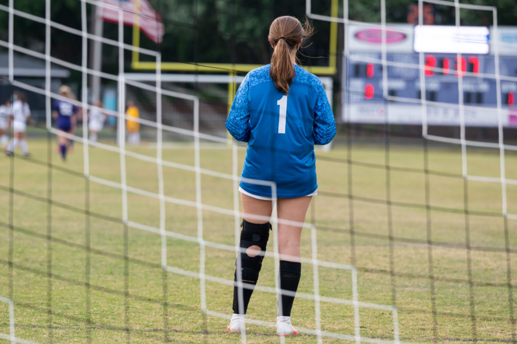 A high school goalie tends her post at the Millbrook High School versus Broughton High School soccer game in spring of 2021.  Photo by Maya Reagan, Carolina Journal