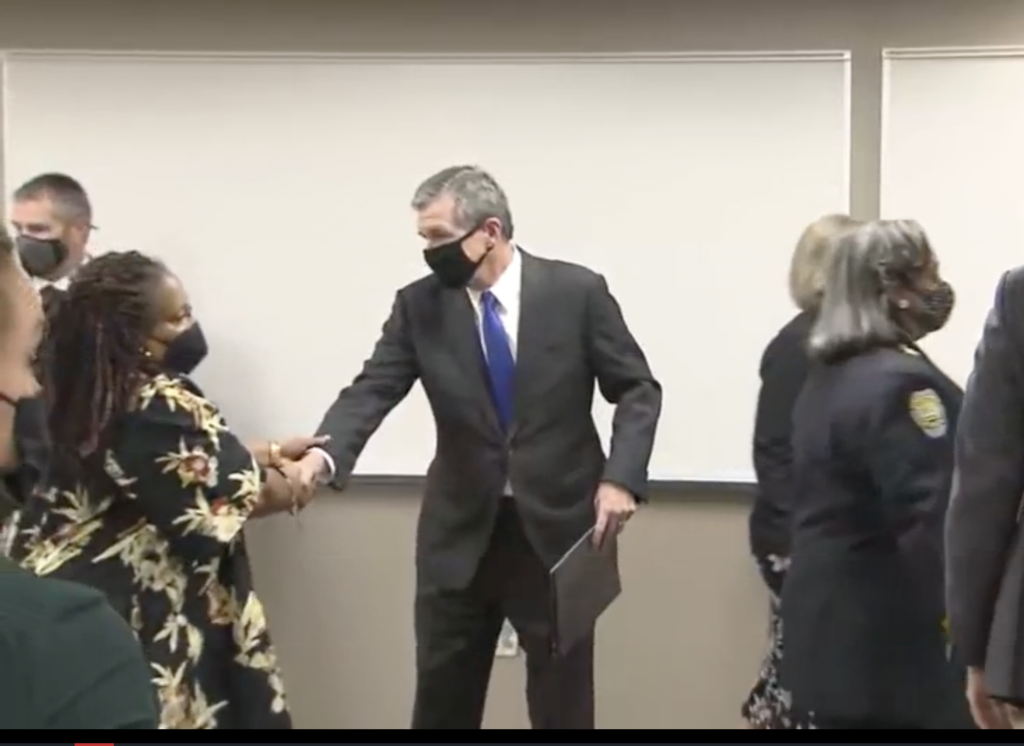 Gov. Roy Cooper greets community members at a press conference folllowing a shooting at Mount Tabor High School in Winston Salem.(image from press conference live stream)