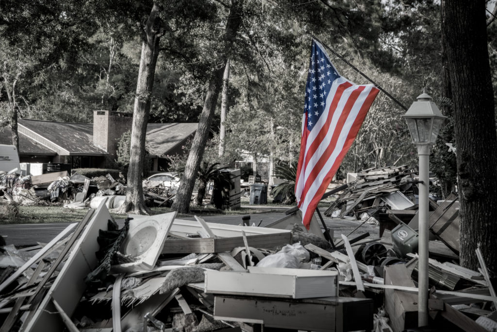 American Flag next to a pile of trash from a home that was hit by Hurricane Harvey.