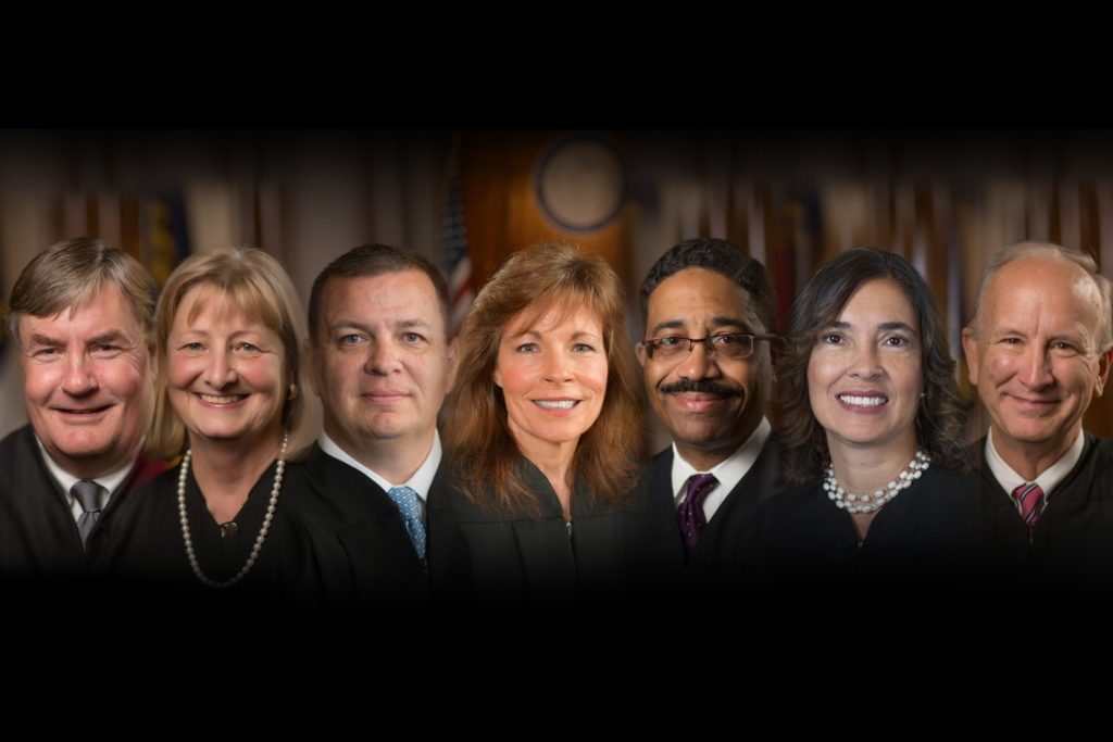N.C. Supreme Court justices, left to right, Associate Justice Samuel Ervin IV, Associate Justice Robin Hudson, Associate Justice Phil Berger Jr., Associate Justice Tamara Barringer, Associate Justice Michael Morgan,  Associate Justice Anita Earls, and Chief Justice Paul Newby