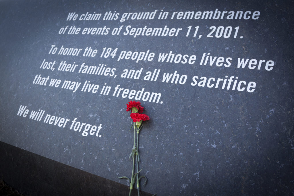 Red carnations lying against the granite wall of the Memorial Gateway entrance to the Pentagon Memorial dedicated to the victims of the Sept. 11, 2001 attack. (Glynnis Jones/Shutterstock)