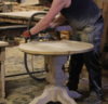 One of our carpenters sanding a Round Pedestal Table top.