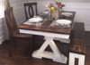 """5.5'x37"""" Trestle Table with a traditional top and endcaps stained in Vintage Dark Walnut in a Semi-Gloss Sheen with an Ivory painted base, a matching Farmhouse bench in Vintage Dark Walnut and Ivory, and two Elizabeth Chairs in Dark Walnut."""