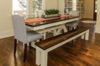 """7' x 37"""" Trestle Table with a jointed top stained Dark Walnut with a semi-gloss sheen. Table features an apron and base painted Ivory. Pictured with a Farmhouse Bench and Grace Dining Chairs."""