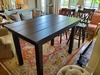 """5' X 37"""" Farm Table, Natural Open Knots in Kona Finish. Also featured Double X-Back Swivel Stool 30"""" Seat Height in Kona Finish."""
