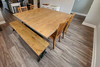 """6' Industrial Steel X-Base Bench in Harvest Wheat with Open / Natural Knots. Also featured 72"""" Square Shiloh Industrial Pedestal Table in Harvest Wheat finish with Filled Knots."""