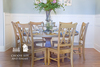 """66"""" round x 30"""" H Knotty Alder Round Top Heirloom Pedestal Table in Harvest Wheat Finish with all top knots filled with epoxy. Also pictured our Double X-Back Dining Chairs in Harvest Wheat finish"""