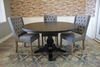 """54"""" Round Pedestal Table with Natural Open Knots in Charred Ember Finish. Also pictured our Lauren Tufted Linen Chair."""