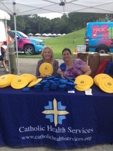Catholic Health Services Love-In Party in the Park Group Image At Table Holding Frisbee
