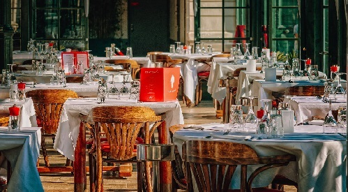 Restaurant dining room, wood chairs, white tablecloths, red menus and red rose on each table.