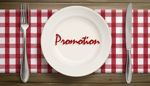 Dinner plate with the word promotion in the center, on table with place setting and red and white checked tablecloth
