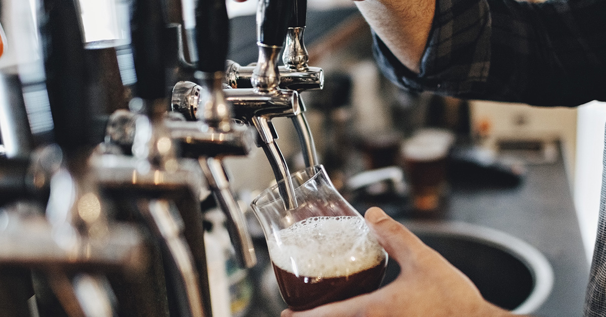Male hand pulling down on beer tap and pouring a dark beer into glass.