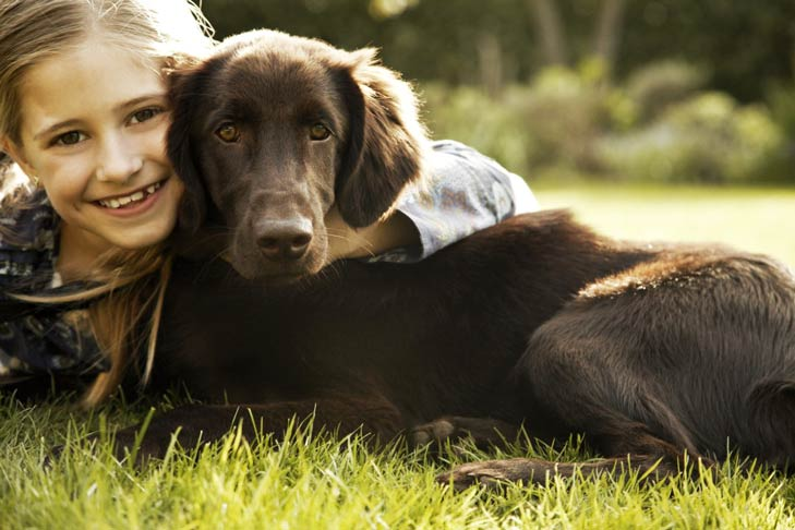 Flat coated retriever and girl hugging outside