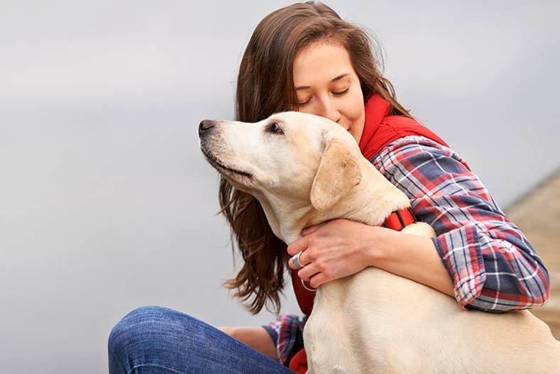 Woman outside with yellow labrador retriever
