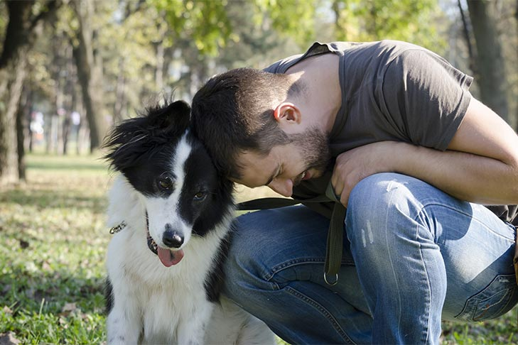 Man snuggling with a Border Collie outdoors.