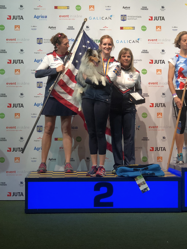Jennifer and Swift stand on the awards podium after winning a silver medal at the FCI World Agility Championship.