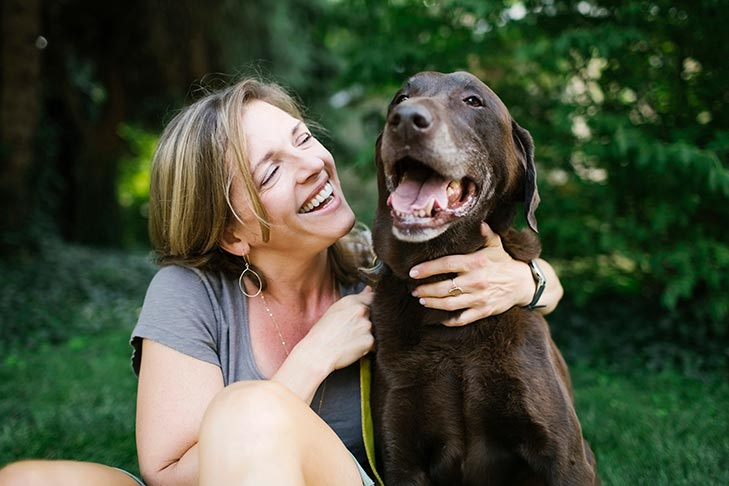 Labrador retriever being hugged by a woman sitting next to it.