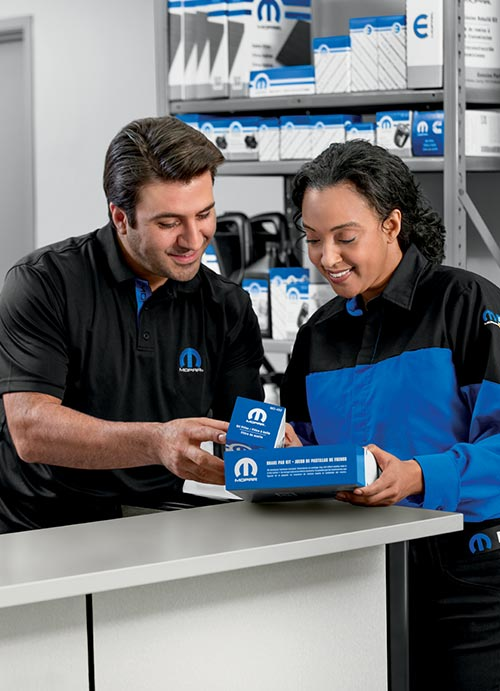 Two employees look at aftermarket parts.