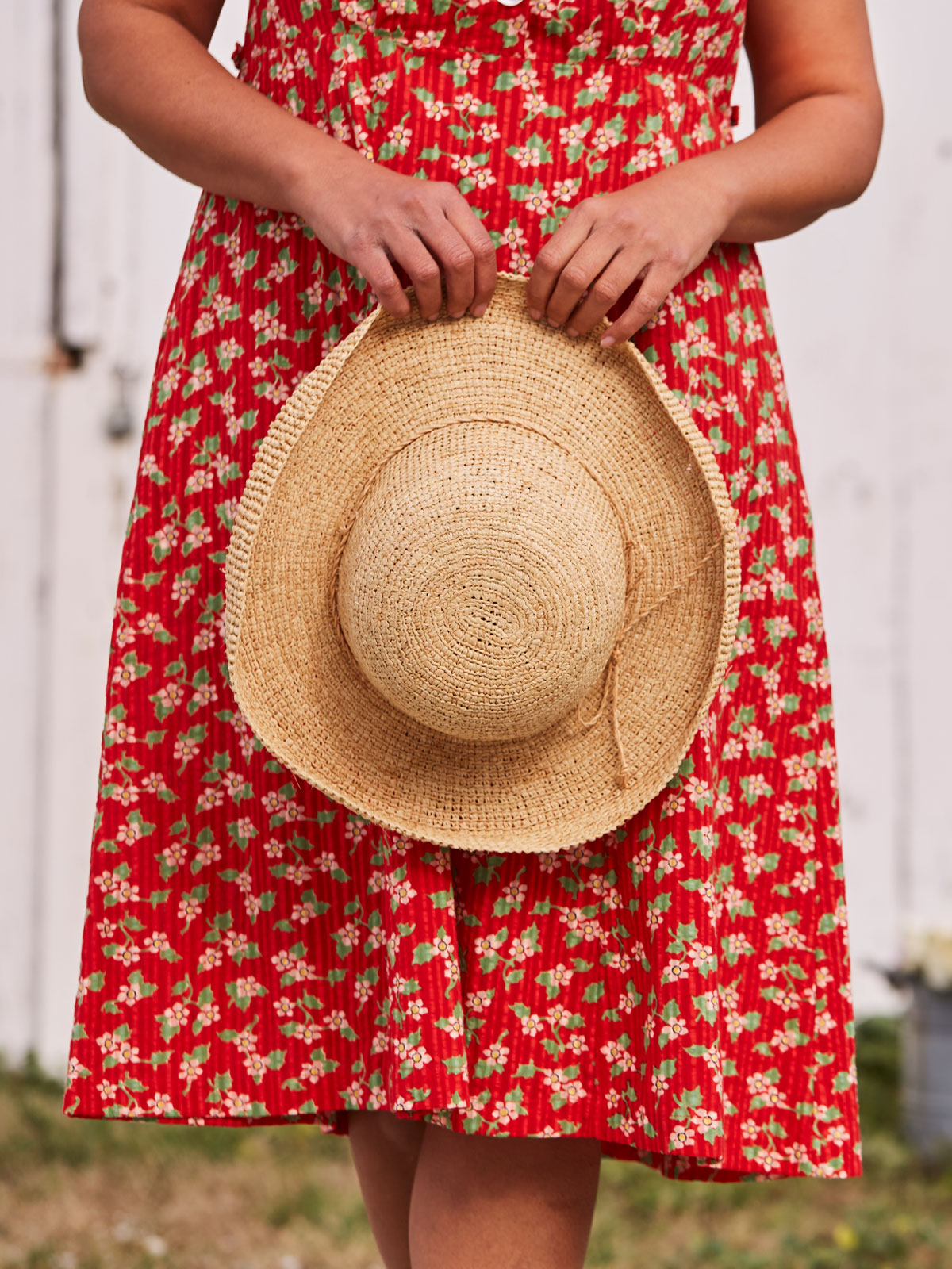 a woman in a red dress holding a hat