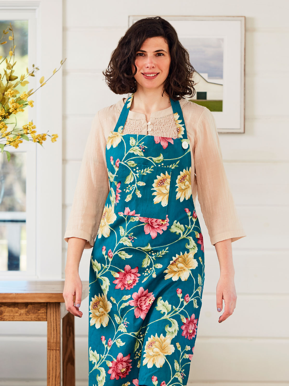 Woman wearing the Rosehip Chef Apron in Teal.