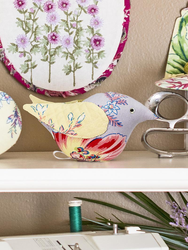Bird Pin Cushion sitting on a shelf.