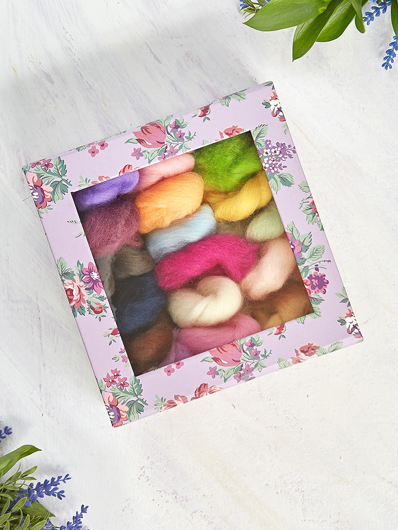 Colorful bundles of wool roving in a small box.