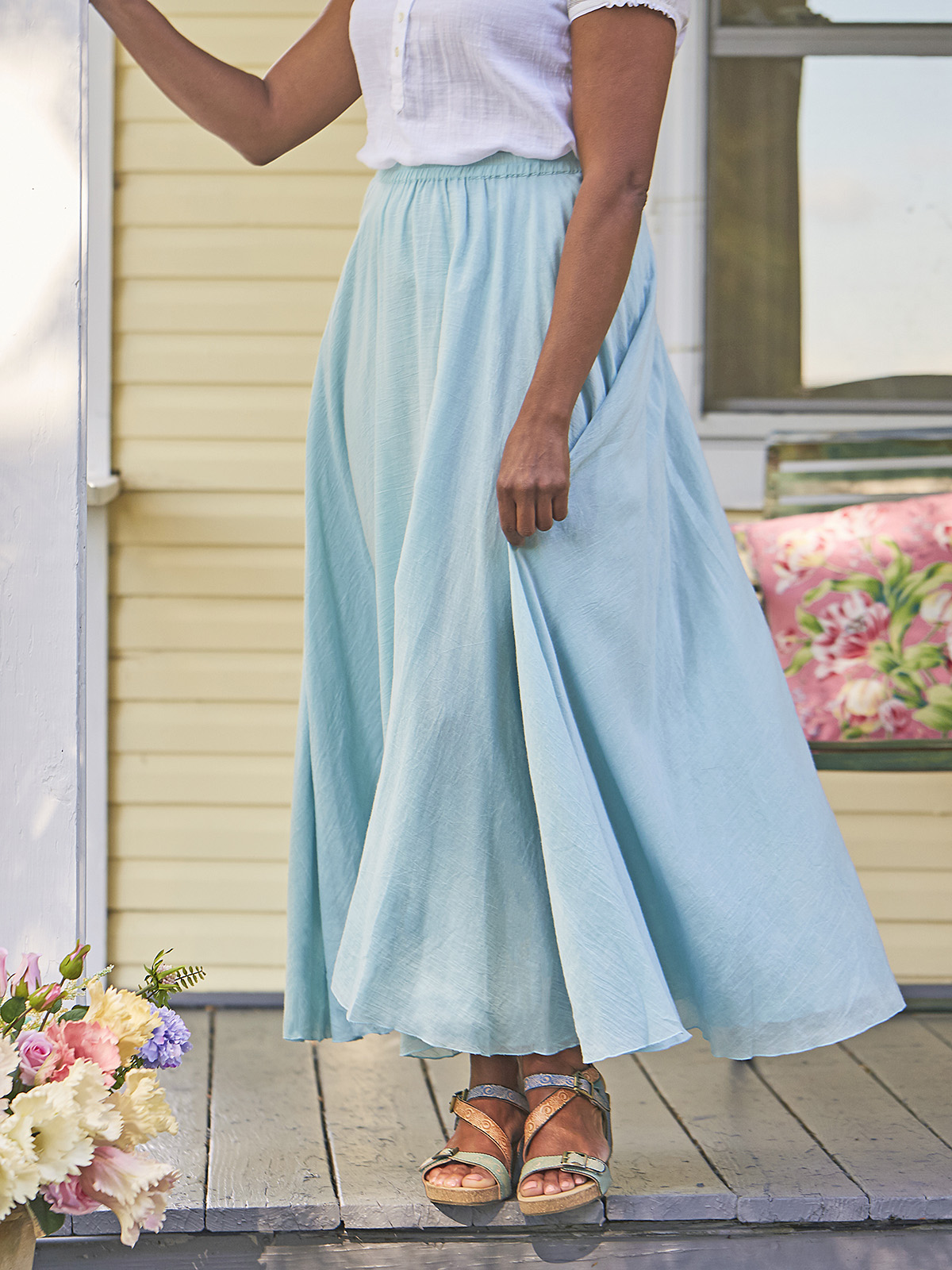 Woman in Aqua colored skirt standing on a porch.