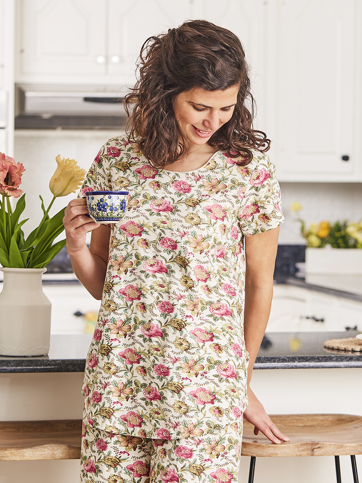 Woman holding a coffee in the kitchen.