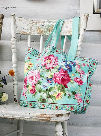 An floral aqua cotton bag sitting on a white porch chair