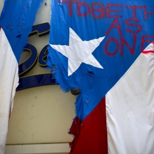 """A damaged Puerto Rican national flag spray painted with the words """"Together as One"""" hangs from the facade of a business, in San Juan, Puerto Rico, Wednesday, Sept. 27, 2017. The relief effort from Hurricane Maria in Puerto Rico has so far been concentrated largely in San Juan, and many outside the capital say they've received little or no help. (AP Photo/Ramon Espinosa)"""